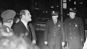 Quebec Justice Minister Jerome Choquette passes Quebec Provincial police security as he enters the courthouse in Montrael, Oct 18, 1970, to pay his respects to fellow cabinet minister Pierre Laporte. THE CANADIAN PRESS/ Stf