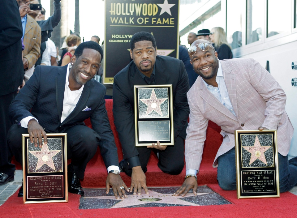 The R&B group Boyz II Men, from left, Shawn Stockman, Nathan Morris and Wanya Morris, touch their new star on the Hollywood Walk of Fame at dedication ceremonies in Los Angeles Thursday, Jan. 5, 2012. (AP / Reed Saxon)