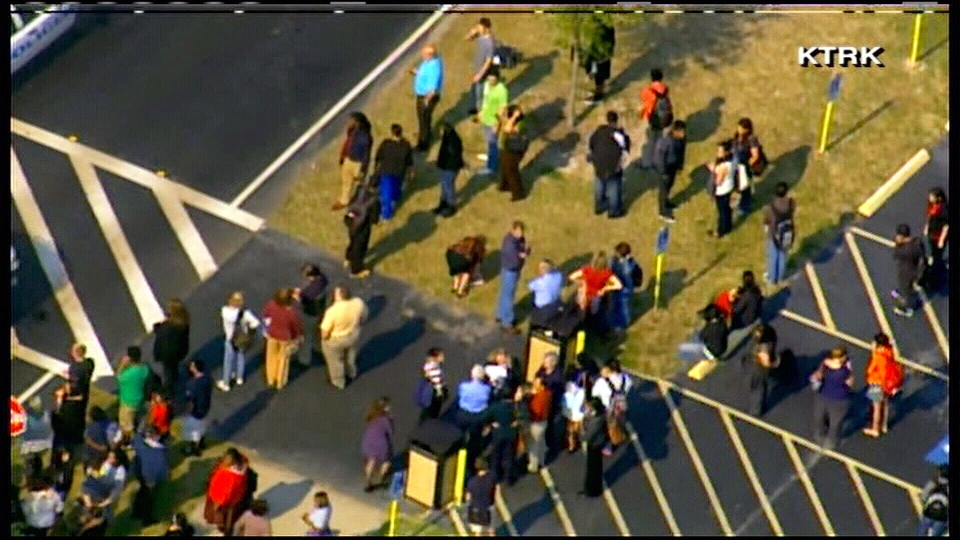 People gather outside the Lone Star College System campus, where there are reports of a shooter on the grounds, in Houston, Tx., Tuesday, Jan. 22, 2013.