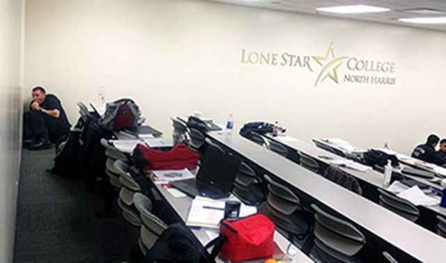 A man hides in a classroom that is on lockdown at Lone Star College, in Houston, Tuesday, Jan. 22, 2013. (Santi Carmona)