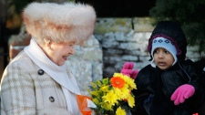 A child gives Britain's Queen Elizabeth II flowers as she leaves after attending the British royal family's traditional Christmas Day church service in Sandringham, England, Saturday, Dec. 25, 2010. (AP / Matt Dunham)