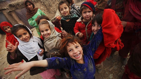 An Afghan refugee girl, bottom, reacts while gathering with other girls in a poor neighborhood of Rawalpindi, Pakistan, Wednesday, Jan. 27, 2010. (AP Photo/Muhammed Muheisen)