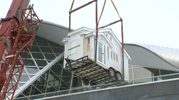 A scale model home, part of a new exhibit at the Art Gallery of Alberta, made an unusual entrance to the gallery on Tuesday. It had to be lifted by a crane to the third floor terrace of the building.