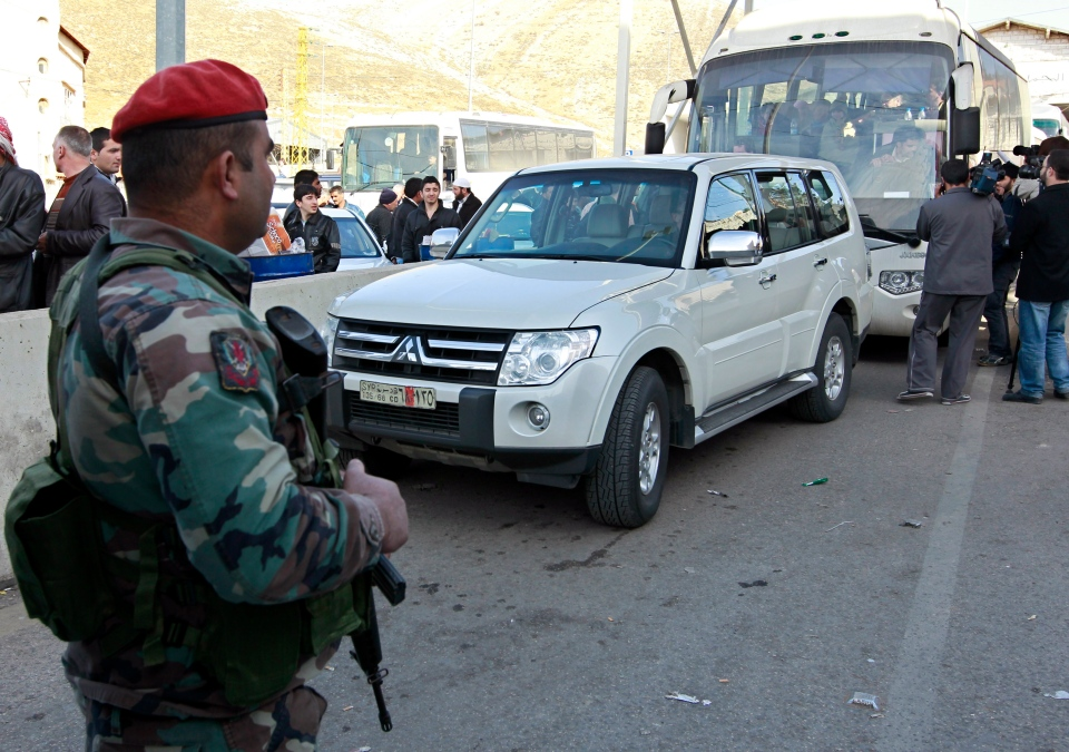 A Lebanese army soldier stands guard as a group of Russian citizens ride inside a bus shortly after crossing the border from Syria into Lebanon at the Masnaa border crossing point, in eastern Lebanon, Tuesday, Jan. 22, 2013. (AP / Bilal Hussein)
