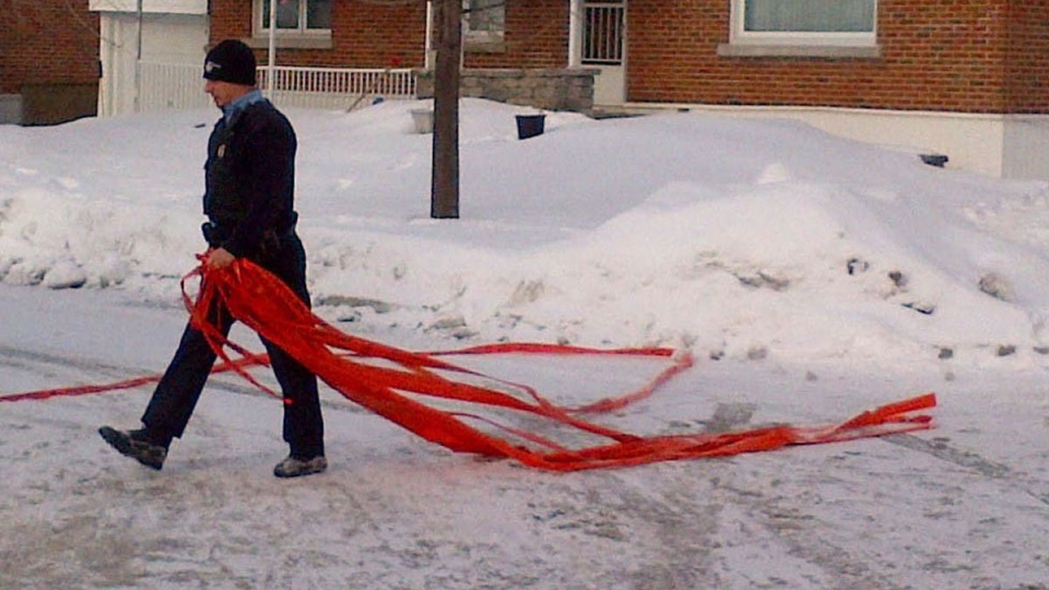 A police officer takes down police tape after a shooting incident in Dorval, Que., Tuesday, Jan. 22, 2013. (Peter Ray / THE CANADIAN PRESS)