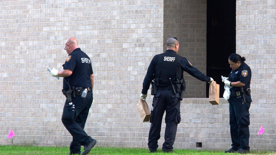Police collect evidence after a shooting happened on Lone Star College North Harris campus in Houston on Tuesday Jan. 22, 2013. (AP / Patric Schneider)