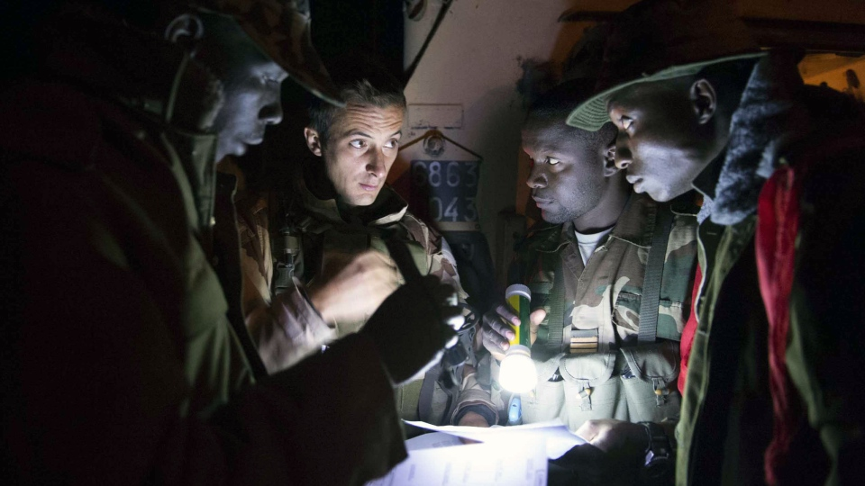 In this picture dated Jan. 20, 2013 and released by the French Army Communications Audiovisual office (ECPAD) a French soldier checks a map with Malian soldiers as they conduct operations in the bush between Markala and Diabali, central Mali. (AP Photo / Arnaud Roine, ECPAD)