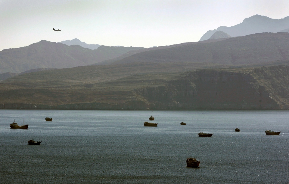 In this Thursday, Jan. 19, 2012 file photo, a plane flies over the mountains in south of the Strait of Hormuz as the trading dhows and ships are docked on the Persian Gulf waters near the town of Khasab, in Oman.  (AP Photo/Kamran Jebreili, File)