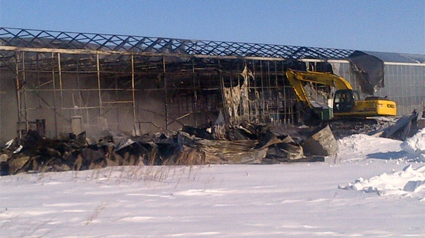 Crews work at the greenhouse site near Otterburne, Man. after a blaze tore through the structure on Jan. 23, 2013.