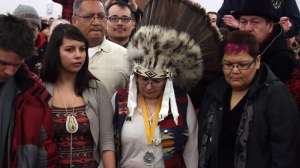 Attawapiskat Chief Theresa Spence, centre, wearing a headdress, takes part in a drum ceremony before departing a Ottawa hotel to attend a ceremonial meeting at Rideau Hall with Gov. Gen. David Johnston in Ottawa, Friday, Jan. 11, 2013. (Fred Chartrand / THE CANADIAN PRESS)