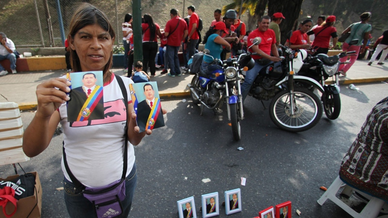 A street vendor shows off her images for sale of Venezuela's President Hugo Chavez at an event commemorating the 1958 fall of the country's last dictatorship in Caracas, Venezuela, Wednesday, Jan. 23, 2013. (AP / Fernando Llano)