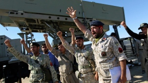 Iranian navy personnel celebrate after successfully launching a Ghader missile from the Jask port area on the shores of the Gulf of Oman during a drill, Tuesday, Jan. 1, 2013.  (AP Photo / Jamejam Online, Azin Haghighi)