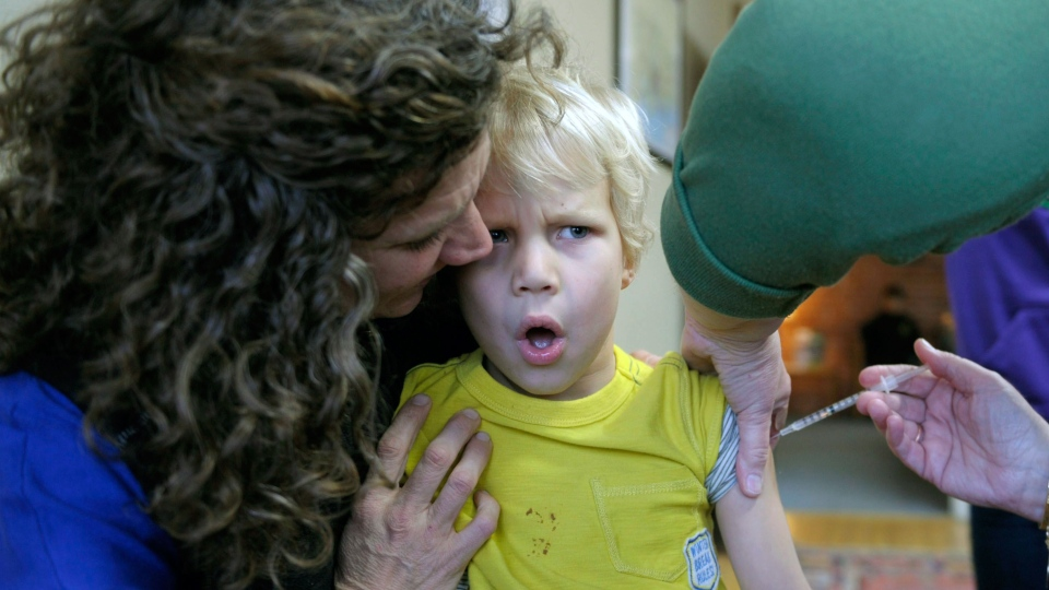 Kris Magnussen, RN, administers the flu vaccine to Alexander Dyjak, 4, as his mother, Ellen, holds him during a vaccination clinic at Ledge Light Health District in New London, Conn., Thursday, Jan. 10, 2013. (AP Photo / The Day, Sean D. Elliot)