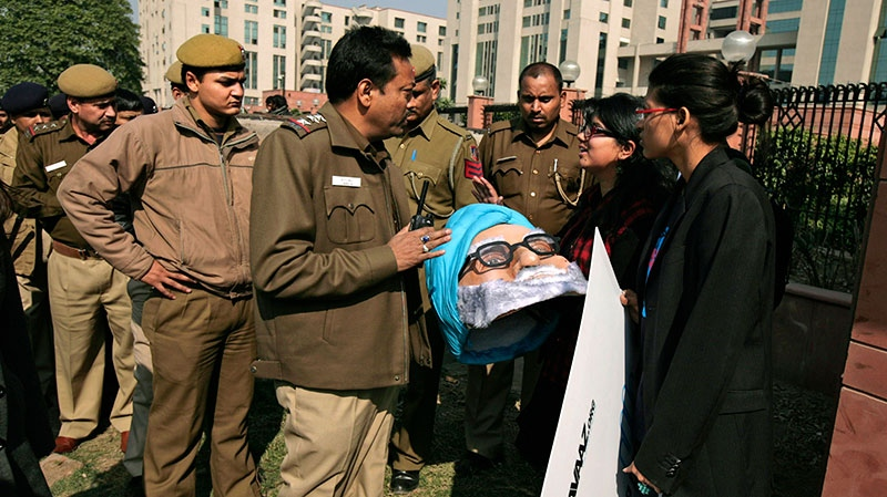 Indian police officials ask activists, holding a mask of Indian Prime Minister Manmohan Singh, to leave as they arrive to protest outside a district court where the accused in the gang rape and murder of a 23-year-old student are undergoing trial, in New Delhi, India, Thursday, Jan. 24, 2013. (AP / Altaf Qadri)