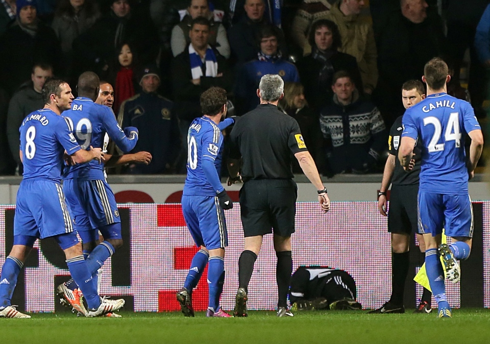 A ball boy, third right, lies on the floor following an incident Chelsea's Eden Hazard, not pictured, as referee Chris Foy, centre in black, makes his way over to calm the situation during the English League Cup second leg semi-final soccer match between Chelsea and Swansea City at the Liberty Stadium, Swansea, Wales, Wednesday Jan. 23, 2013.