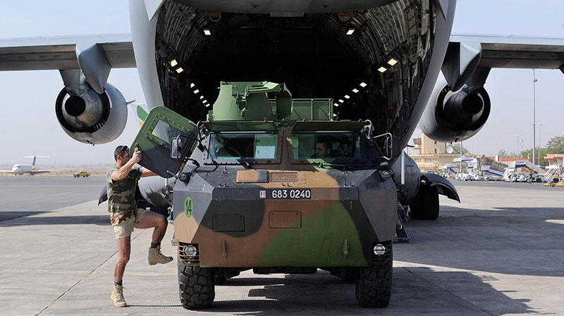A French soldier climbs inside a light armored vehicle as it is unloaded from a Canadian Forces C-17 Globemaster III in Bamako, Mali, on Thursday, Jan. 17, 2013. (Department of National Defence-Sergeant Matthew McGregor, Canadian Forces Combat Camera)