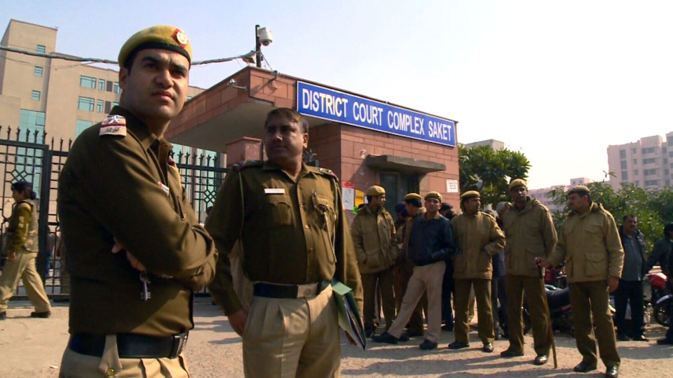 Police stand guard near the gate of a district court where the the men accused in the gang rape of a 23-year-old student are undergoing trial in New Delhi, India, Thursday, Jan. 24, 2013.