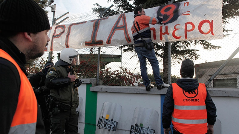 A striking Metro worker paints a banner which reads in Greek '9 days on strike' as a riot police officer looks on near the entrance of subway train depot, in Athens, on Friday, Jan. 25, 2013.  (AP / Petros Giannakouris)