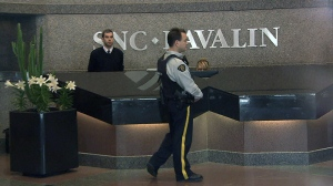 A police officer paces in the lobby of SNC-Lavalin in Montreal, April 13, 2012.