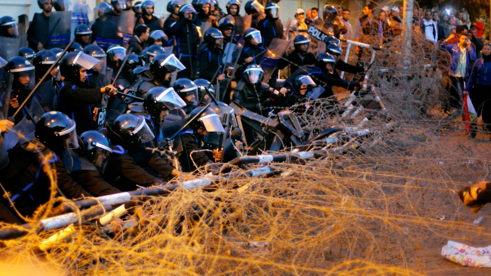 Egyptian anti-riot policemen resist protesters from pulling barbed wire in front of the presidential palace in Cairo, Egypt, Friday, Jan. 25, 2013. (AP / Amr Nabil)