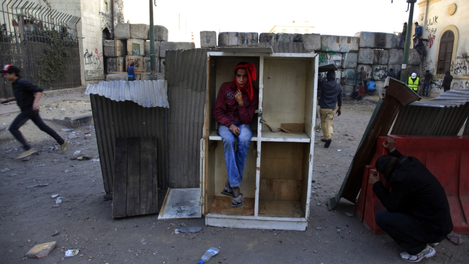 Egyptian protesters hide for cover during clashes with riot police, not seen, near Tahrir Square, Cairo, Egypt, Friday, Jan. 25, 2013. (AP / Khalil Hamra)