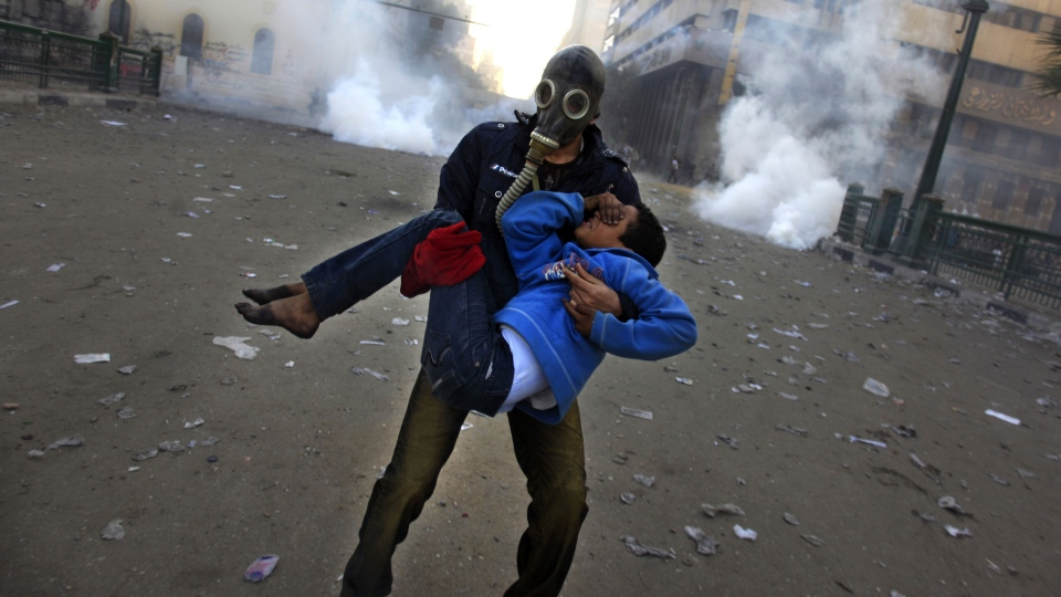 An Egyptian protester evacuates an injured boy during clashes near Tahrir Square, Cairo, Egypt, Friday, Jan. 25, 2013. (AP / Khalil Hamra)
