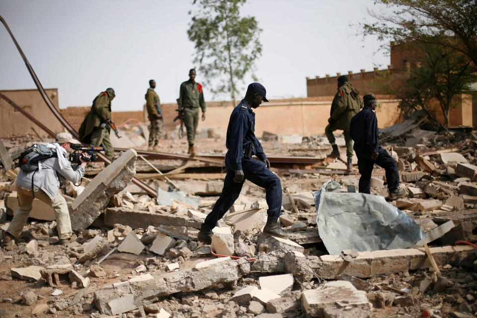 In this image taken during an official visit organized by the Malian army to the town of Konna, some 680 kilometers north of Mali's capital Bamako, Saturday, Jan. 26, 2013, a videographer films Malian soldiers walking through the rubbles of a former army based leveled during fighting with Islamist rebels. (AP / Jerome Delay)