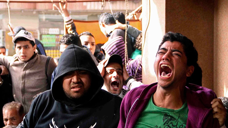 Families and supporters of those accused of soccer violence react to the announcement of verdicts for 21 fans on trial in last year's Port Said stadium incident which left 74 people dead, in Port Said, Egypt, Saturday, Jan. 26, 2013. (Mohammed Nouhan, Shorouk Newspaper)