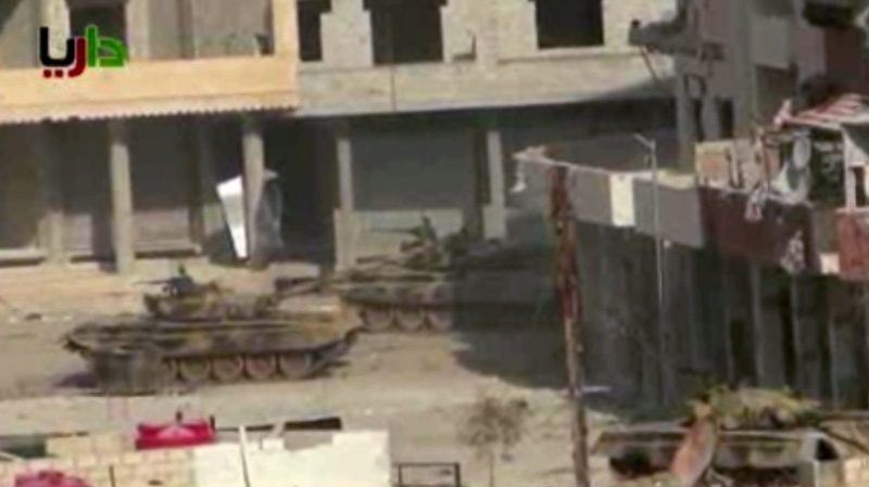 In this image taken from video obtained from the Sham News Network, which has been authenticated based on its contents and other AP reporting, a pair of what activists say are tanks from President Bashar Assad regime in sit in a street in the Daraya neighborhood of Damascus, Syria, just before one of them fires a shot Friday, Jan. 25, 2013. (AP / Sham News Network via AP video)