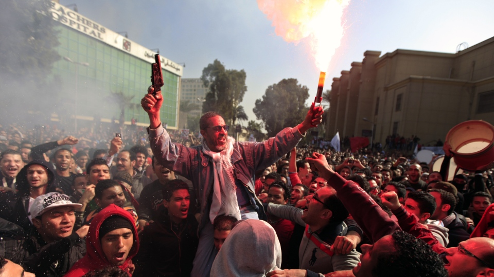 Egyptian soccer fans of Al-Ahly club celebrate a court verdict that returned 21 death penalties in last years soccer violence, inside the club premises in Cairo, Egypt, Saturday, Jan. 26, 2013. (AP Photo / Khalil Hamra)