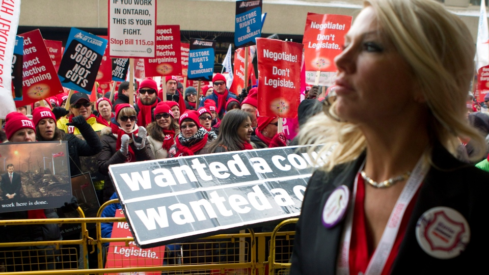 An Ontario Liberal Party delegate walks past protesters as they gather outside Toronto's Maple Leaf Gardens on Saturday, January 26, 2013 while the party gathers to vote for a new provincial leader and in turn a new premier of Ontario. (Chris Young /THE CANADIAN PRESS)