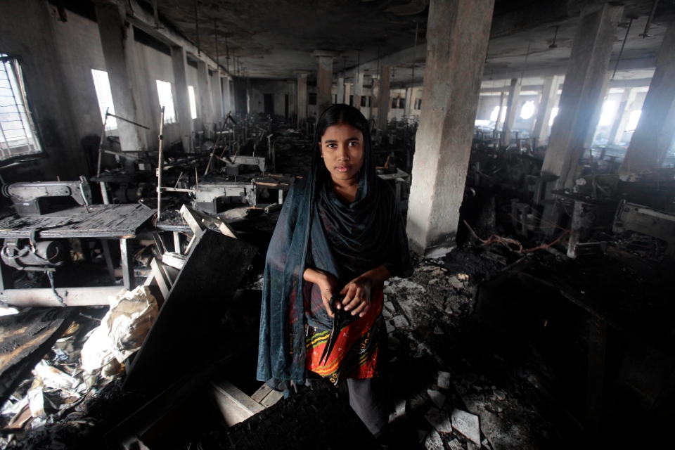 Bangladeshi garment worker Laiju stands inside the damaged Smart Export Garment Ltd. factory where a fire Saturday claimed the lives of seven of her female colleagues in Dhaka, Bangladesh, Sunday, Jan. 27, 2013. (AP / A.M. Ahad)