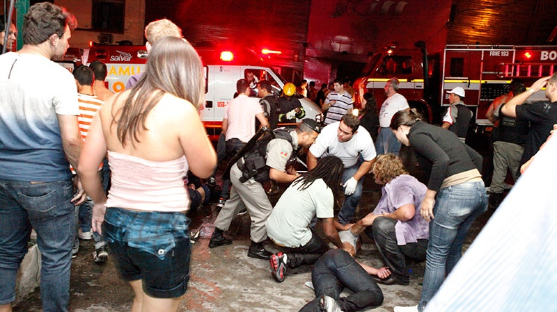 People help an injured man, victim of a fire in a club in Santa Maria city, Brazil, Sunday, Jan. 27, 2013. (AP / Agencia RBS)