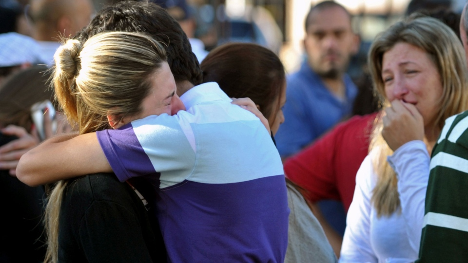 Relatives of victims react near the Kiss nightclub in Santa Maria city, Rio Grande do Sul state, Brazil, Sunday, Jan. 27, 2013. (AP / Ronald Mendes-Agencia RBS)