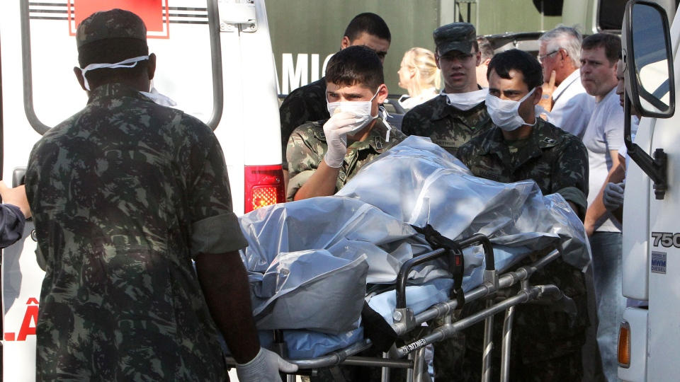 Brazil's soldiers carry the remains of a victim outside a gymnasium where bodies were brought for identification in Santa Maria city, Rio Grande do Sul state, Brazil on Sunday, Jan. 27, 2013. (AP / Nabor Goulart)