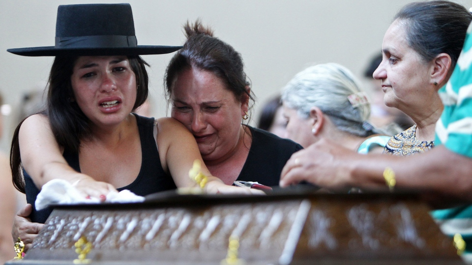 Relatives cry next to a coffin at a gymnasium where bodies were brought for identification in Santa Maria city, Rio Grande do Sul state, Brazil on Jan. 27, 2013. (AP / Nabor Goulart)