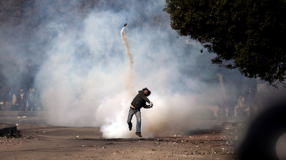 An Egyptian protester throws a tear gas canister back at riot police, not seen, during clashes near Tahrir Square, Cairo, Egypt on Sunday, Jan. 27, 2013. (AP / Khalil Hamra)