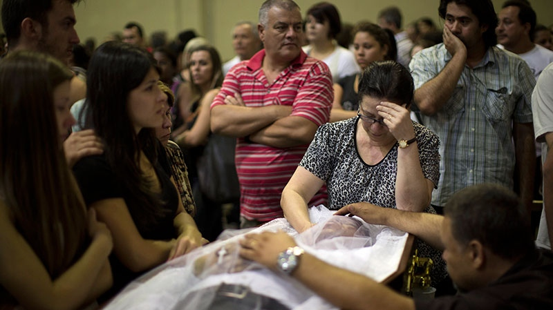 Relatives and friends mourn on the coffin containing the remains of a fire victim at a gymnasium where bodies were brought for identification in Santa Maria city, Rio Grande do Sul state, Brazil, Sunday, Jan. 27, 2013. (AP / Felipe Dana)