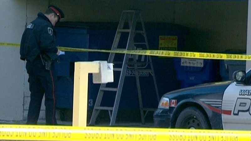 Police investigate a dumpster where a human torso was found in Kitchener, Ont., on Sunday, Jan. 27, 2013.