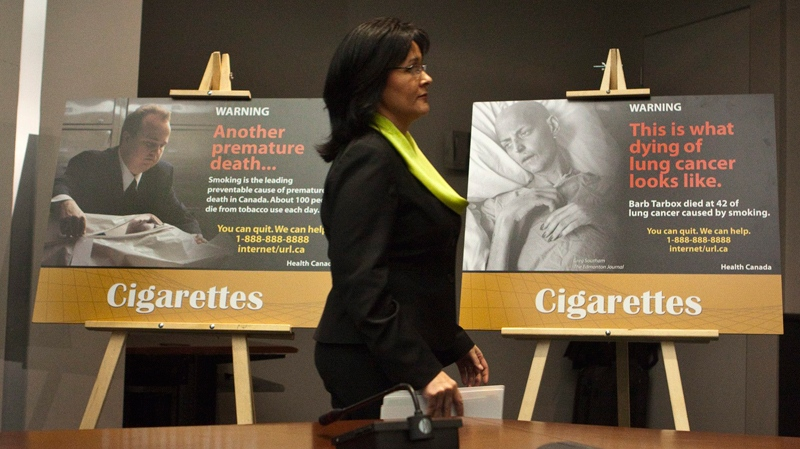 Health Minister Leona Aglukkaq walks by new cigarette packaging images during a news conference in Ottawa on Thursday, Dec. 30, 2010. (Pawel Dwulit / THE CANADIAN PRESS)