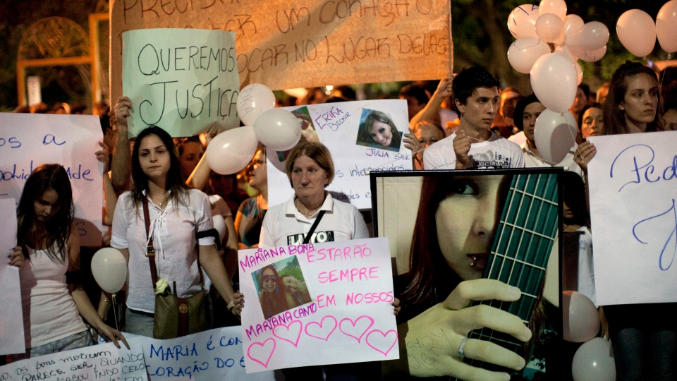 People march near the Kiss nightclub honouring the victims of early Sunday's fatal fire inside the club in Santa Maria, Brazil, Monday, Jan. 28, 2013. (AP Photo / Felipe Dana)