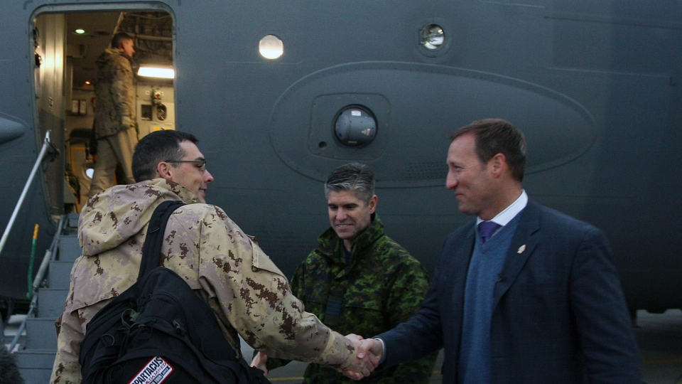 Minister of Defence Peter MacKay shakes hands with a Canadian Forces member of the 429 squardon at CFB Trenton, in Trenton, Ont. on Tuesday, Jan. 15, 2013. (AP / Felipe Dana)