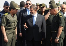 Abdel-Fattah el-Sissi, left, speaks with Morsi.