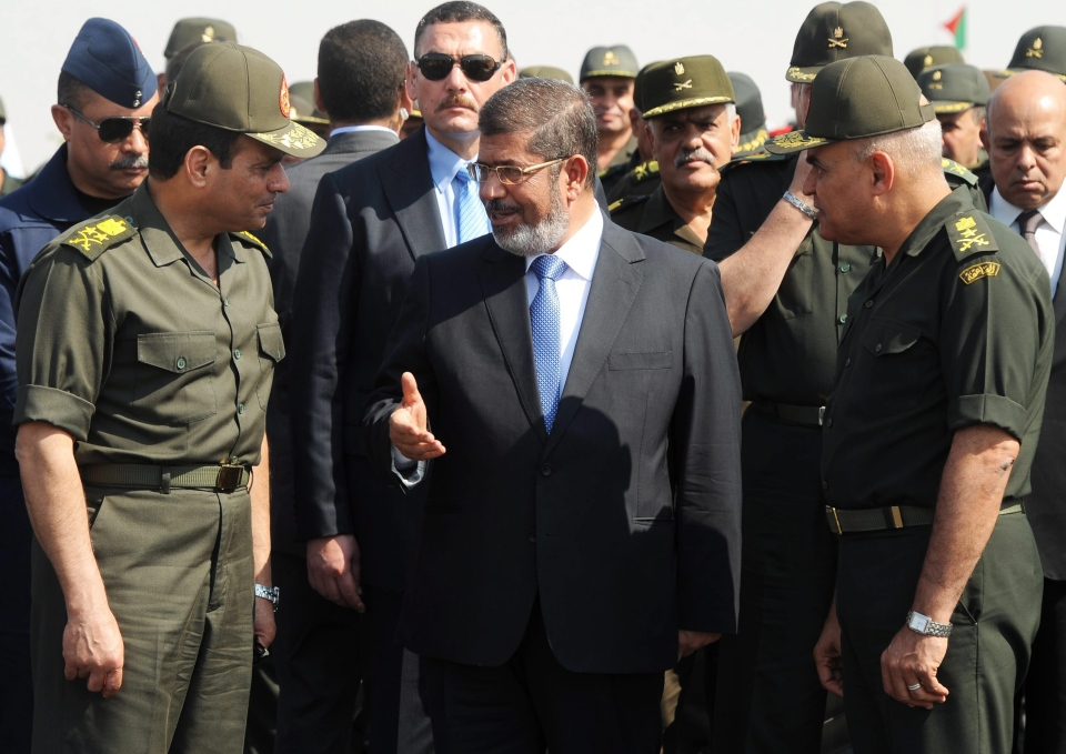 In this image released by the Egyptian Presidency, Egyptian President Mohammed Morsi, centre, speaks with Minister of Defence, Lt. Gen. Abdel-Fattah el-Sissi, left, at a military base in Ismailia, Egypt, Wednesday, Oct. 10, 2012. (AP Photo/Egyptian Presidency)