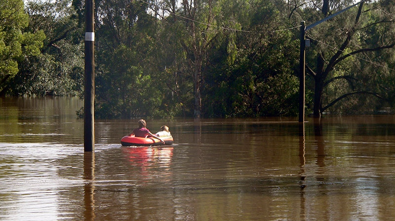 In this photo supplied by NSW State Emergency Service, two children ride on a boat in floodwaters caused by torrential rains in Lismore, northern New South Wales, Australia Tuesday, Jan. 29, 2013. (NSW State Emergency Service / Samantha Cantwell)