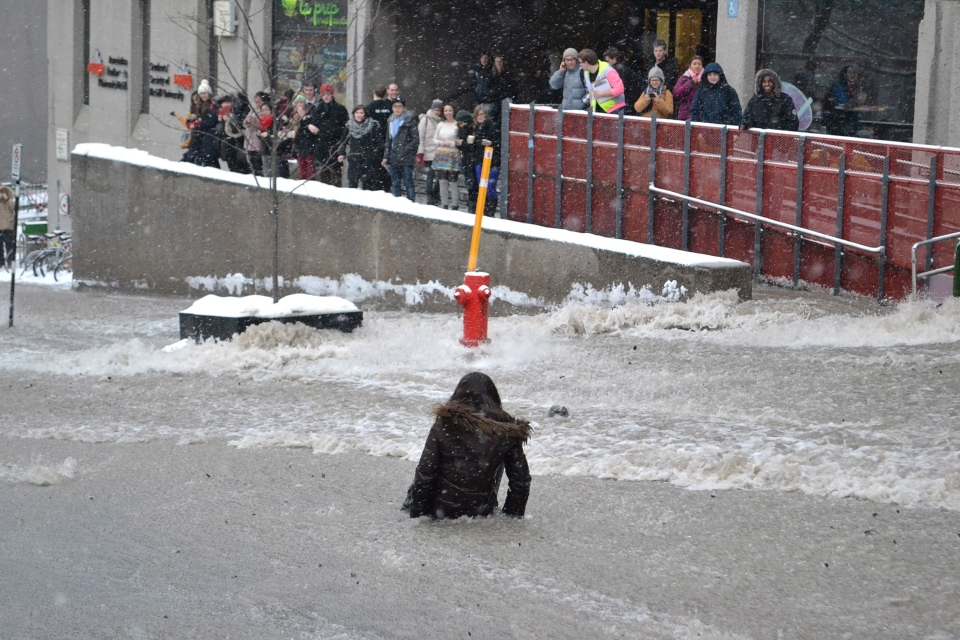 A woman is swept in current down McTavish Street after a water main break in Montreal on Monday January 28, 2013. THE CANADIAN PRESS/Ian Howarth