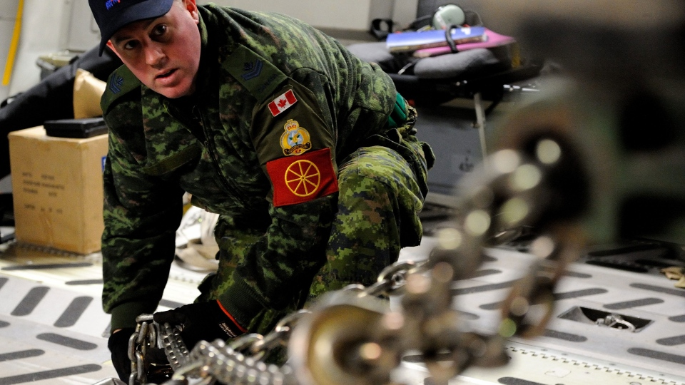 A Canadian Forces traffic technician uses a chain to secure a French military light armored vehicle inside a Canadian Forces CC-177 Globemaster III aircraft on Jan. 27, 2013 (Sgt.  Matthew McGregor / Canadian Forces Combat Camera)