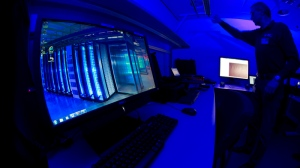 A member of the Cybercrime Center turns on the light in a lab during a media tour at the occasion of the official opening of the Cybercrime Center at Europol headquarters in The Hague, Netherlands, Friday Jan. 11, 2013. (AP / Peter Dejong)