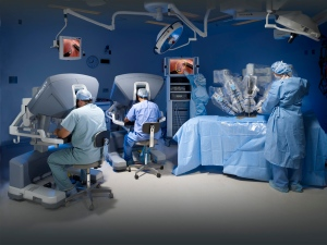 A horizontal action shot shows an operating room featuring the da Vinci Si Surgical System. (Courtesy Intuitive Surgical Inc.)