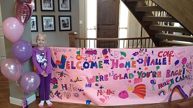 Six-year-old Halle Popowich stands with a banner welcoming her back home, after undergoing a life-saving bone-marrow transplant. SUPPLIED.